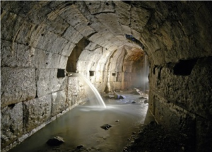 a round stone tunnel with water in the bottom - Roman sewers