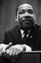 Martin Luther King, Jr: a black man at a podium
