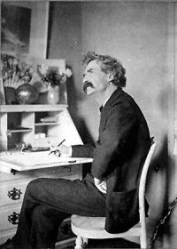 Mark Twain: a white man with shaggy hair sitting at a desk in a suit