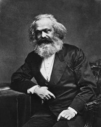 Karl Marx, a white man with long white hair and a very bushy beard, wearing a suit