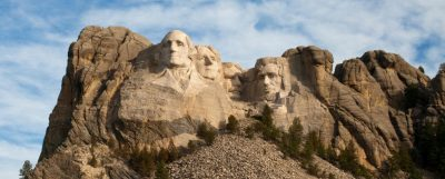 four white men's heads carved into a cliff