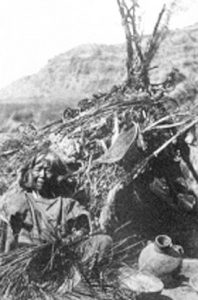 Ute people in front of their wickiup house
