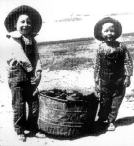 Boys in overalls doing chores on the Oregon Trail