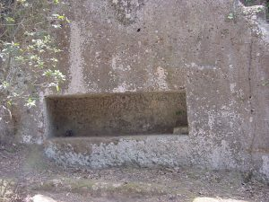 A tomb in the shape of a coffin cut into a cliff wall