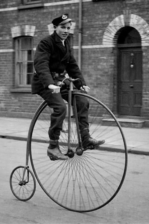"A ""Penny-farthing"" bicycle with one big wheel and one small one, with a boy riding it"