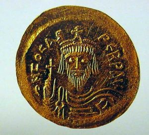 A gold coin showing a bearded man
