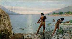 A Native man and woman fishing with nets in a large bay: Native American economy