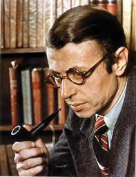 Jean-Paul Sartre - a young white man with dark hair and glasses wearing a suit and smoking a pipe