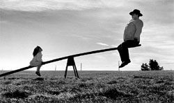A man and a girl on a seesaw
