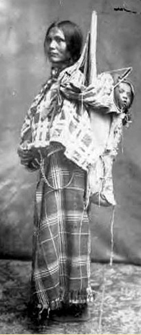 A Native woman with a long braid carrying a baby in a carrier on her back. She wears a shirt and shawl of European fabric. (Shoshone history)