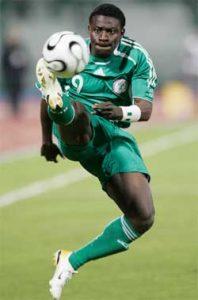 A black soccer player kicking a ball