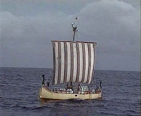 A small ship with red and white striped square sail on the ocean