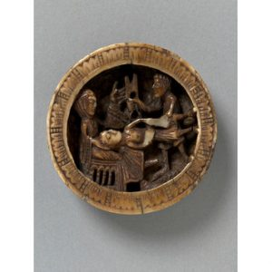 A round piece of brownish ivroy with a woman sitting and a man lying down with his head in her lap. Another man stands in the background - the attendant who brings Delilah the scissors