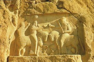 Rock carving in a cliff of two men on horseback fighting: the Sassanians