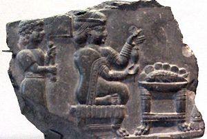An enslaved woman stands behind a free Elamite woman who is spinning (600s BC)