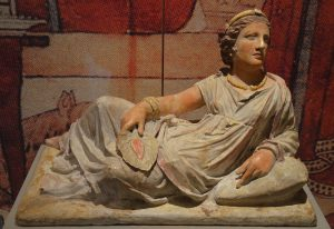 An Etruscan woman on her sarcophagus, holding a hand fan shaped like a leaf