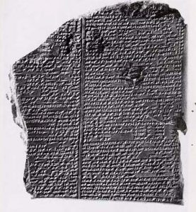 A black and white photo of a cuneiform tablet with tiny writing on it - about the god Enlil