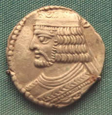 A gold coin showing the head of a white man with four layers of curls, wearing a crown.