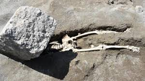 Skeleton in the dirt with a rock over it
