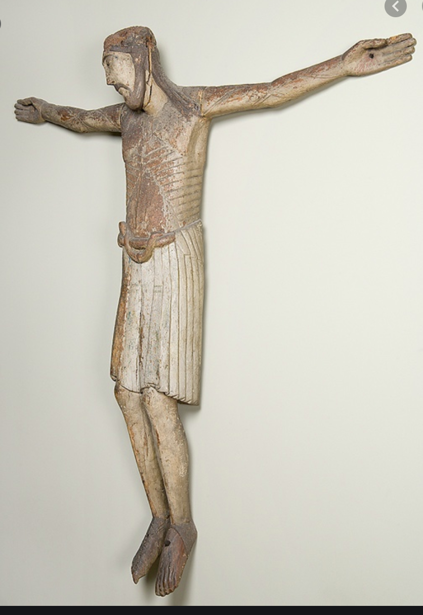 wooden crucifixion with white skirt and knees slightly bent